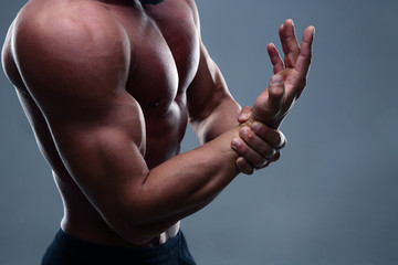 Muscular man with hand pain on gray background