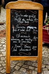 Wooden menu board on sidewalk in France