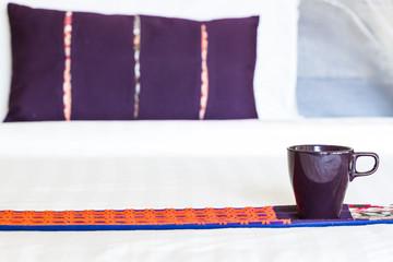violet mug on bed