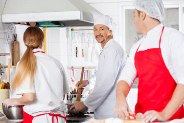 Smiling Chef Working With Colleagues At Kitchen