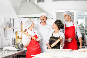 Smiling Chefs Looking At Colleague In Kitchen