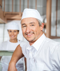 Confident Male Mature Butcher Smiling At Butchery