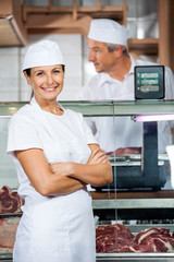 Confident Butcher With Colleague Working In Shop