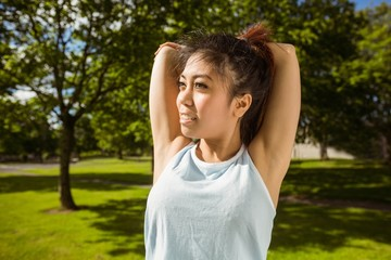 Healthy woman stretching hands in park