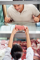 Butcher Showing Fresh Red Meat To Customer