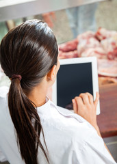 Butcher Using Digital Tablet In Store