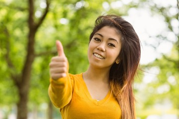 Beautiful woman gesturing thumbs up in park