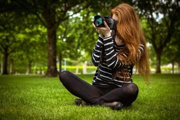 Female photographer sitting on grass
