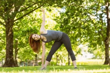 Pretty athletic redhead stretching in park