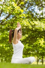 Healthy woman sitting with joined hands over head at park