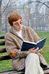 Woman reading a book in the city park