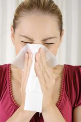 Frau mit Erkältung putzt Nase mit Taschentuch