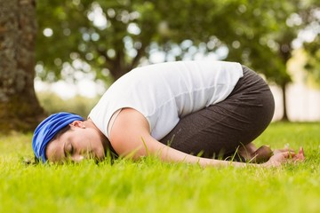 Brunette relaxing and meditating on grass
