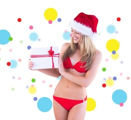 Composite image of festive fit blonde in red bikini showing gift