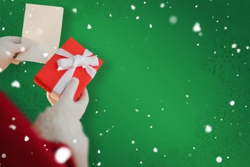 Composite image of father christmas holding a gift