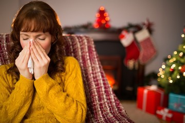 Woman sitting on sofa and blowing her nose at christmas