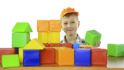 little boy builds a house of children's blocks