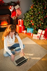 Redhead woman sitting on floor using laptop at christmas