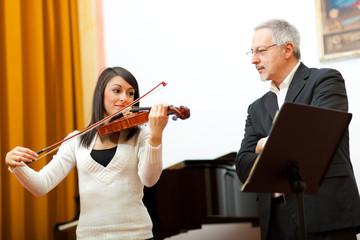 Violin teacher helping a student