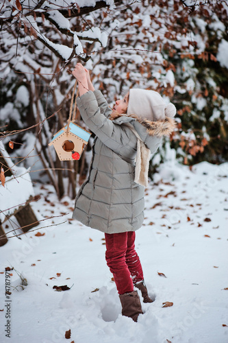 Leinwandbild Motiv child girl hanging bird feeder in winter snowy garden