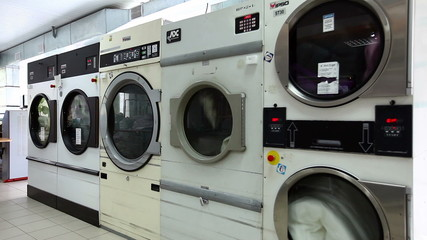 View of running washing machines in laundry room