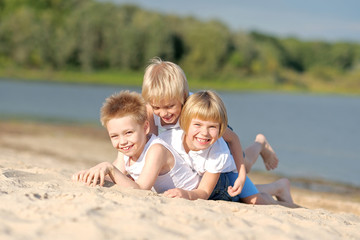 Portrait of three children playing on the beach