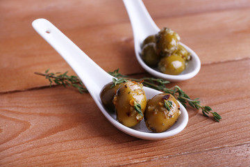 Green olives in oil with spices and rosemary in spoons