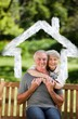 Composite image of mature couple hugging in the garden