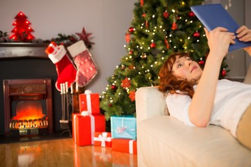 Smiling redhead lying on the couch using tablet