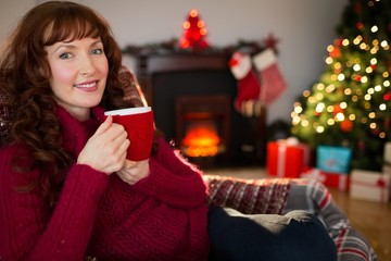 Pretty redhead enjoying hot drink at christmas