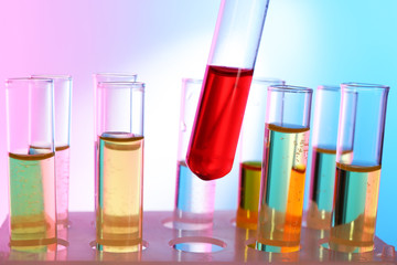 Test tube filled with red liquid on background of other tubes