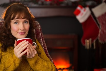Smiling red hair enjoying hot drink at christmas