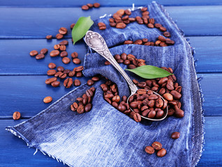 Green petals near the spoon of coffee beans