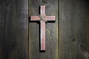 Wooden cross hanging in spotlight on rustic wood background