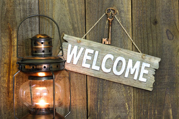 Wood welcome sign by antique lantern and bronze skeleton key