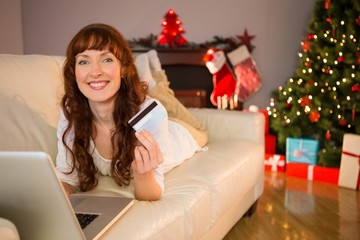 Smiling redhead lying on couch shopping online with laptop