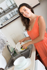 woman washing dishes in domestic kitchen