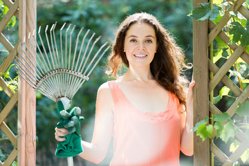 Happy woman with rake
