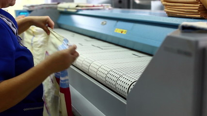 Worker loads bedsheet in ironing machine
