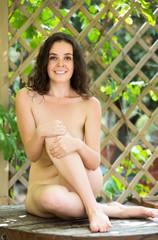 Naked girl posing in garden