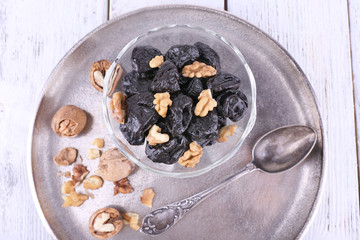 Metal tray with glass bowl of prunes and walnuts, shell and