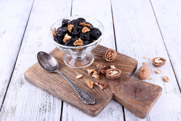 Wooden board with glass bowl of prunes and walnuts, shell and