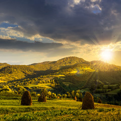 field with haystack on hillside at sunset