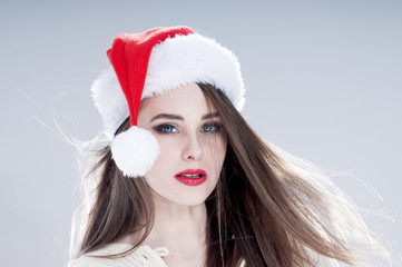 Christmas woman. Beautiful charming girl wearing  santa hat over