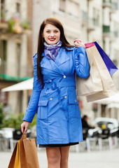 woman in blue cloak with purchases at street