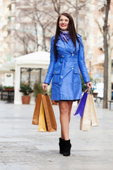 happy woman in  cloak with shopping bags