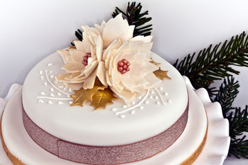 Iced round cake decorated with Christmas roses.