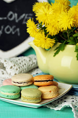 Yellow flowers in decorative teapot and tasty macaroons