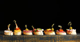 Tasty sandwiches on wooden table, on black background