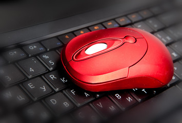 The red computer mouse on the black keyboard